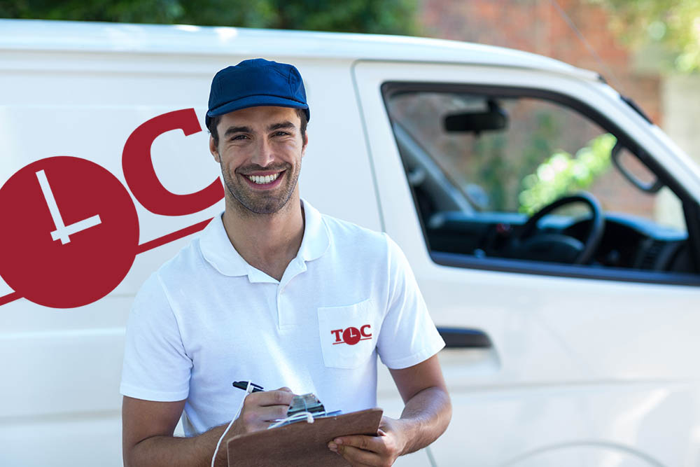 Portrait of happy delivery man with clipboard while standing by van